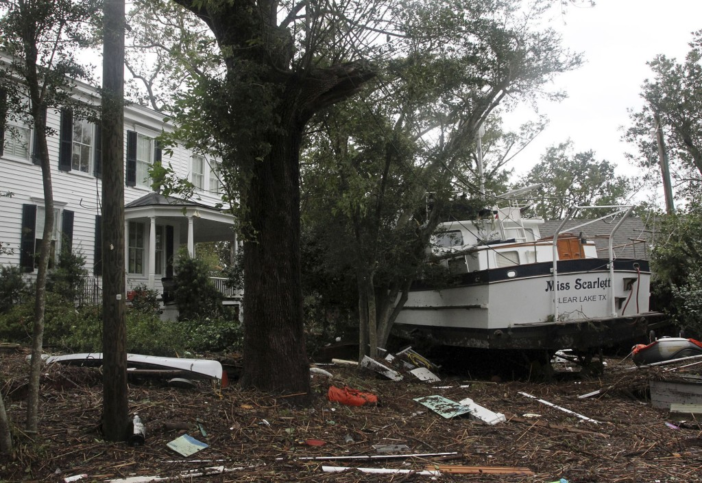 A 40-foot yacht lies in the yard of a storm-damaged home on East Front Street in New Bern, N.C., Saturday, Sept. 15, 2018. The boat washed up with sto
