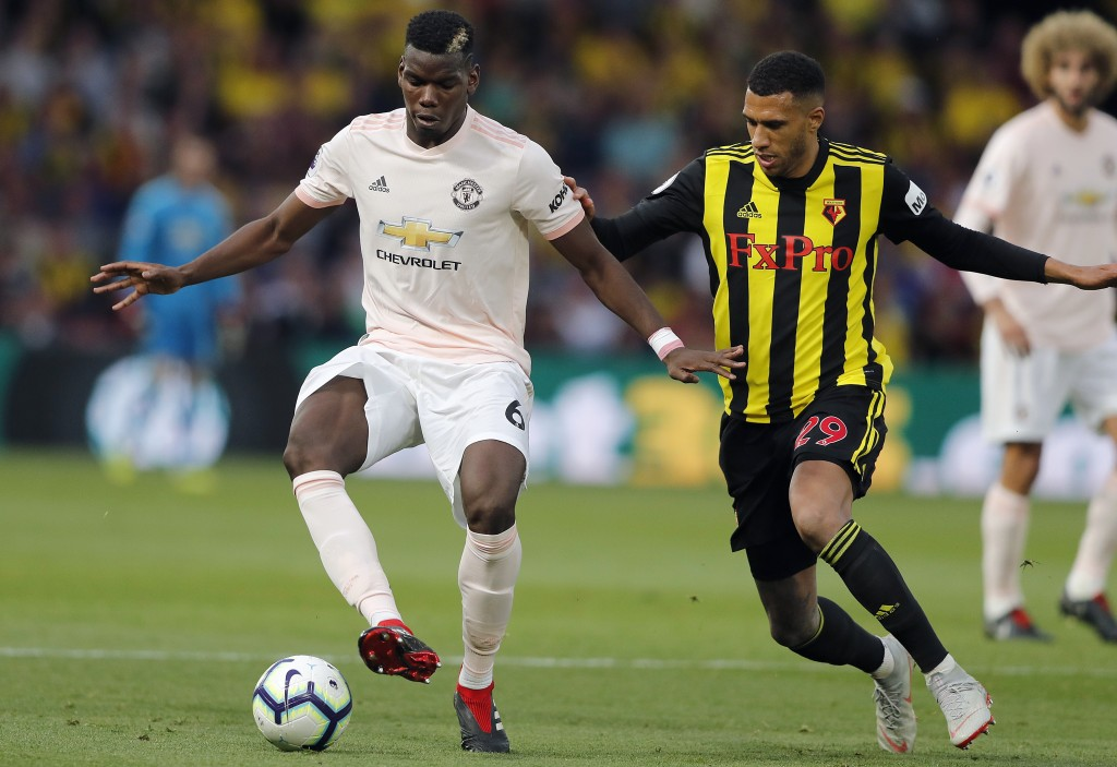 Manchester United's Paul Pogba, left, and Watford's Etienne Capoue challenge for the ball during the English Premier League soccer match between Watfo