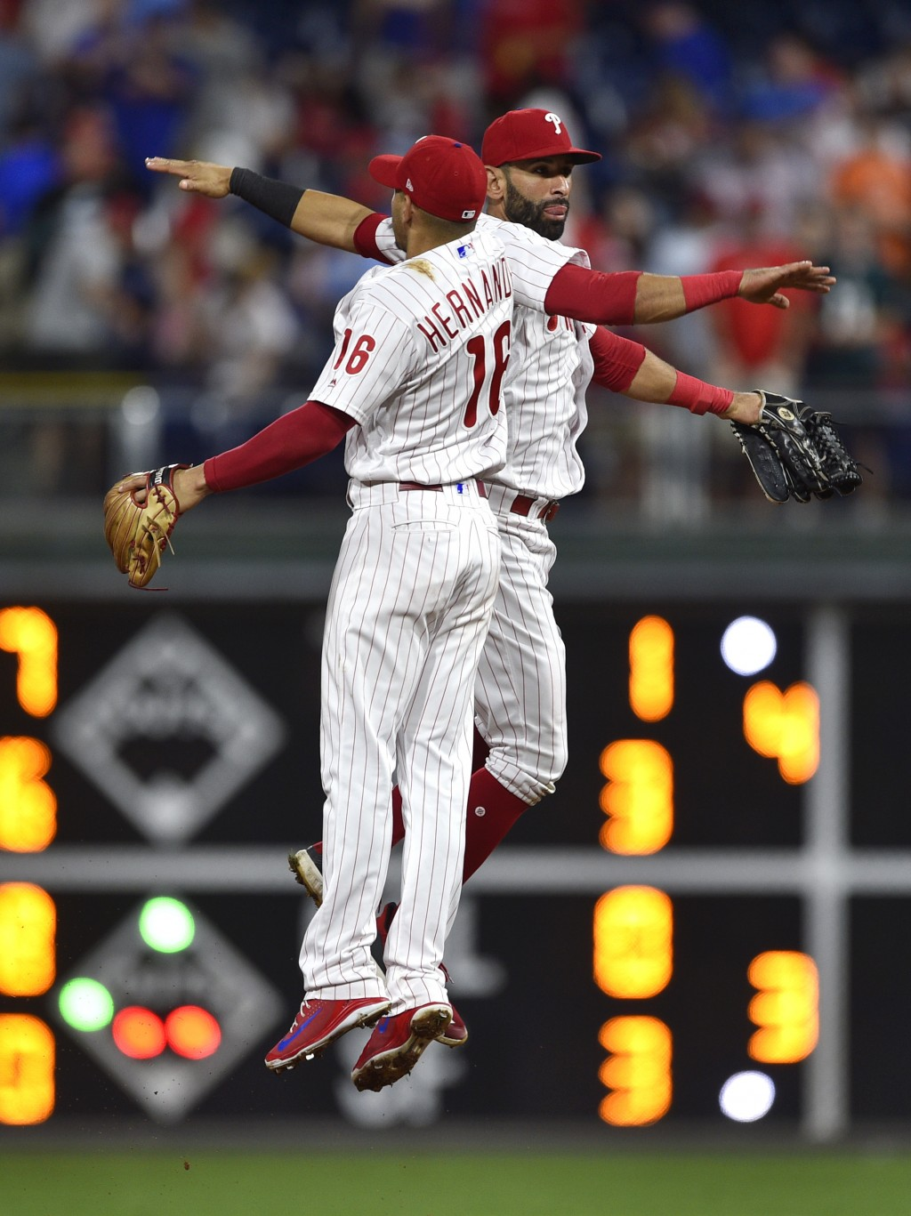 Philadelphia Phillies' Cesar Hernandez (16) and Jose Bautista celebrate a victory over the Miami Marlins, Saturday, Sept. 15, 2018, in Philadelphia. (