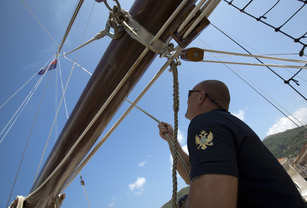 In this Sept. 6, 2018 photo, a sailor pulls rope during a sail aboard the training ship 'Jadran' near the port of Tivat, Montenegro. Montenegro and Cr