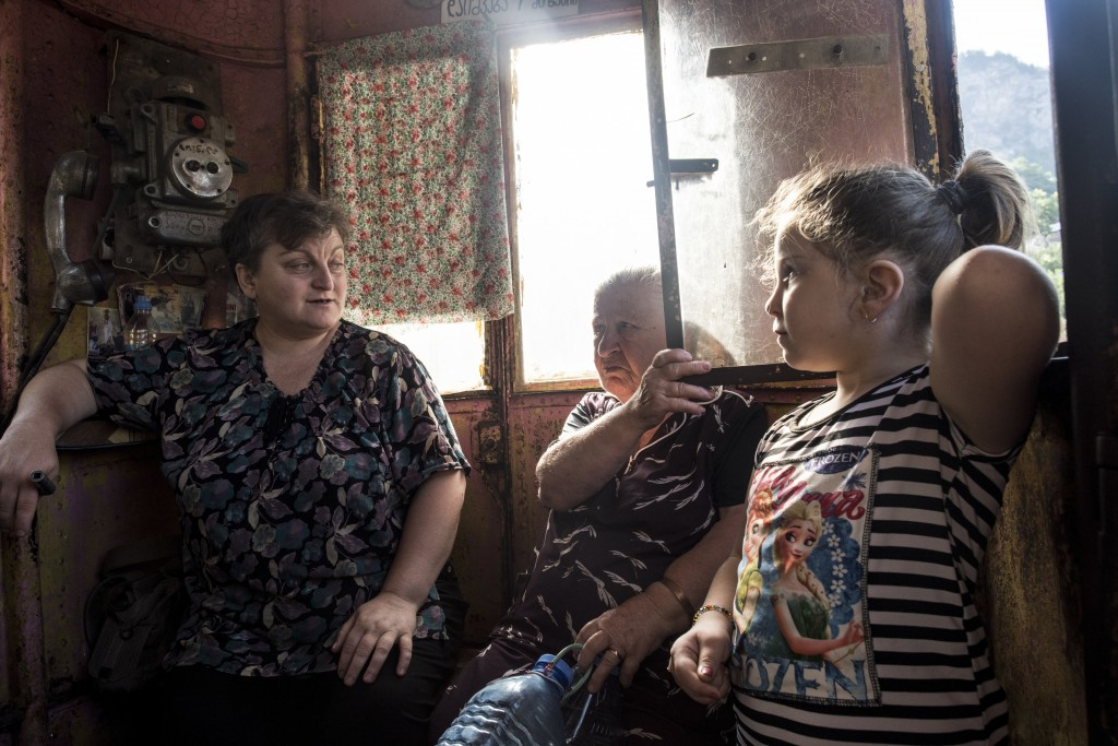 In this photo taken on Friday, Aug. 31, 2018, local residents talk to each other as they ride in a cable car in the Georgian city of Chiatura, about 2...