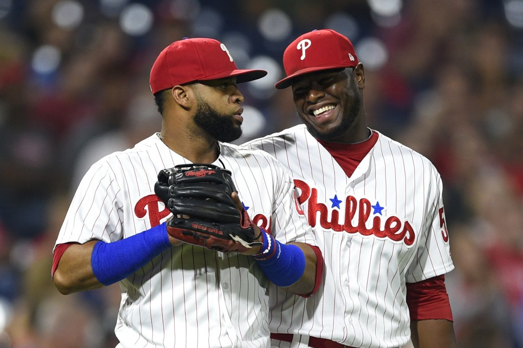 Philadelphia Phillies' Hector Neris, right, smiles after Carlos Santana made a infield catch on a ball hit by Miami Marlins' Rafael Ortega during the