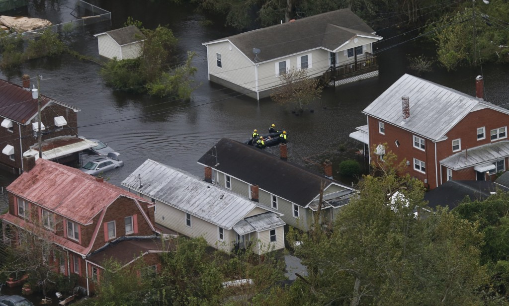 Rescue personnel use a small boat as they go house to house checking for flood victims from Florence in New Bern, NC., Saturday, Sept. 15, 2018. (AP P