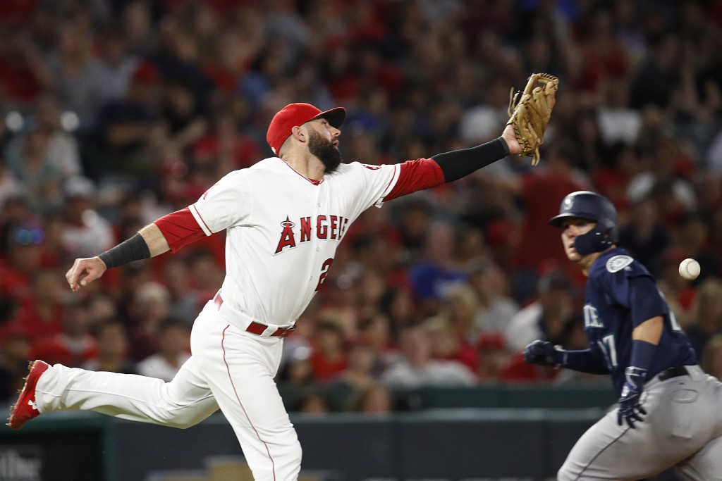 Los Angeles Angels' Kaleb Cowart misses a ground ball hit by Seattle Mariners' Kristopher Negron as Mariners' Ryon Healy, background right, runs to th
