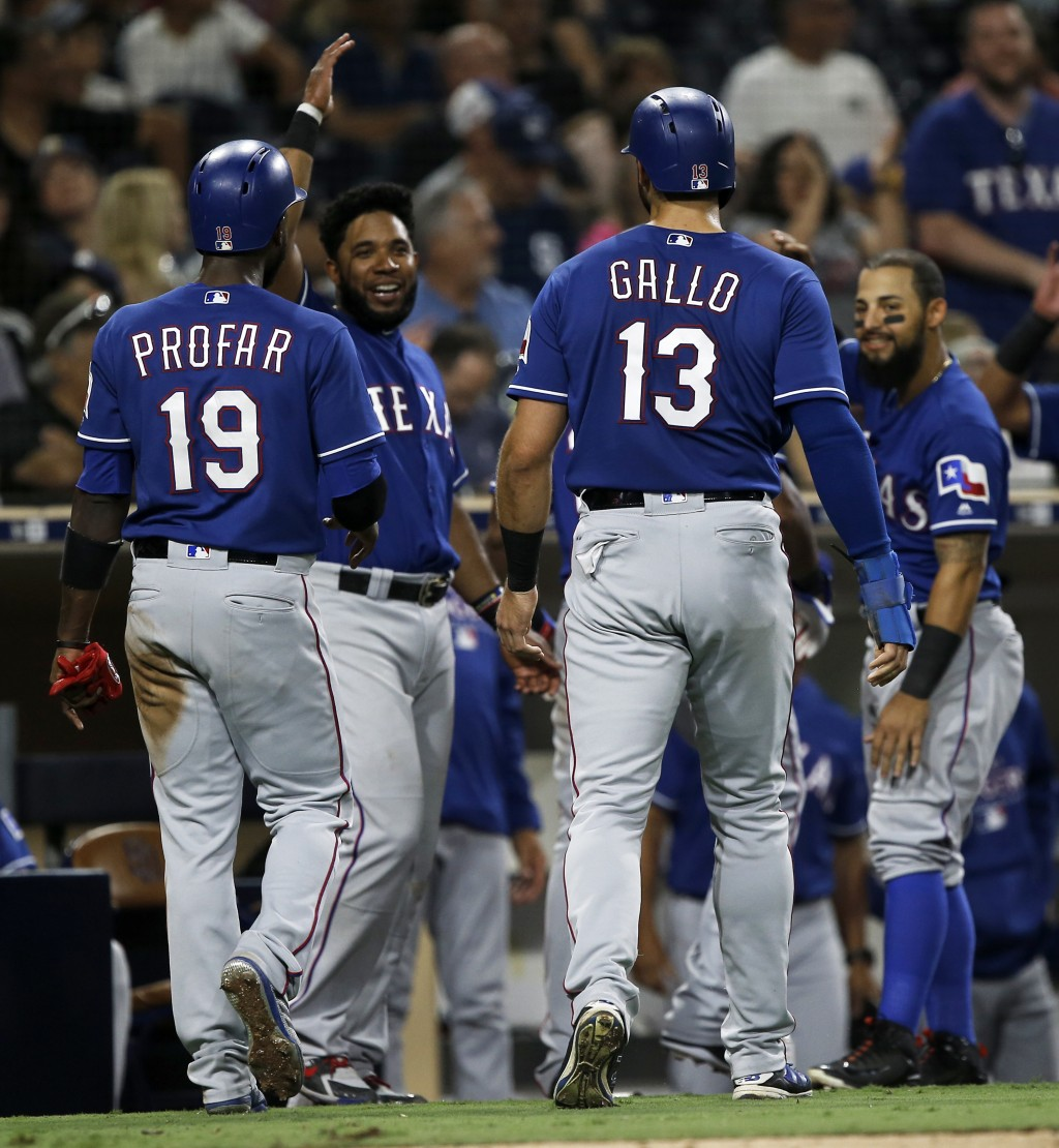 Texas Rangers' Jurickson Profar (19) and Joey Gallo (13) get congratulations from Elvis Andrus, second from left, and Rougned Odor, right, after scori