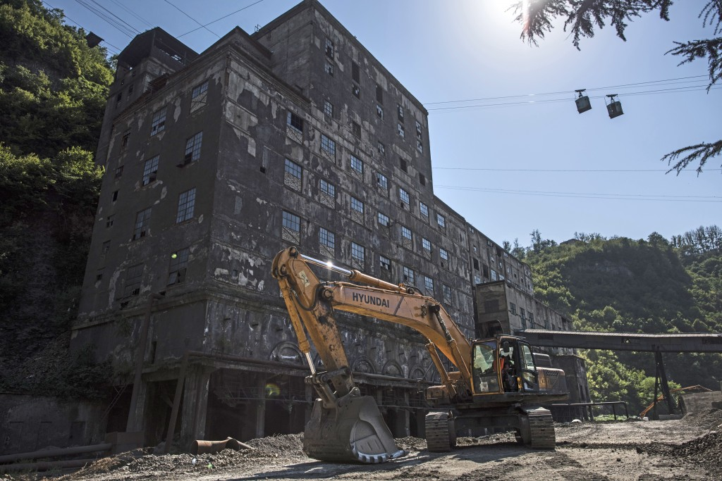 In this photo taken on Wednesday, Aug. 29, 2018, two cable cars move over an abandoned mine building in the Georgian city of Chiatura, about 200 kilom