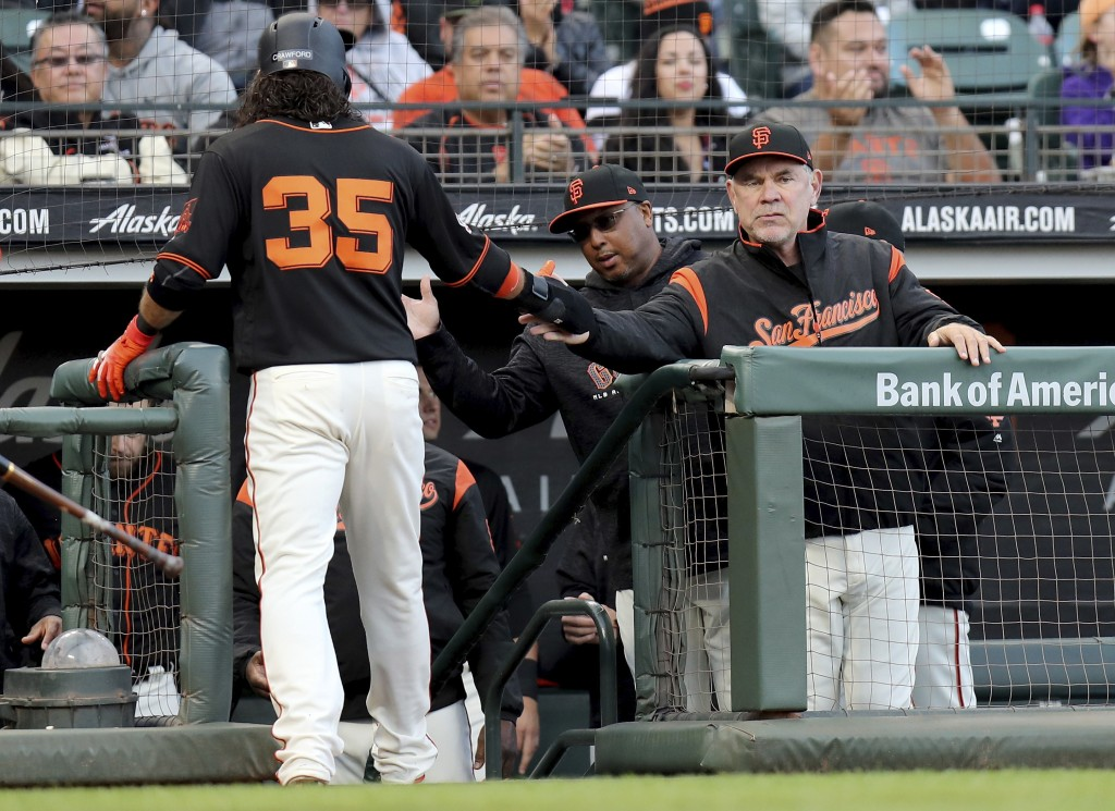 San Francisco Giants manager Bruce Bochy (15) congratulates shortstop Brandon Crawford (35) after scoring in the second inning of a baseball game agai
