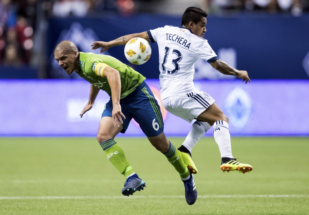 Seattle Sounders' Osvaldo Alonso (6) and Vancouver Whitecaps' Cristian Techera (13) collide during the first half of an MLS soccer match, Saturday, Se...