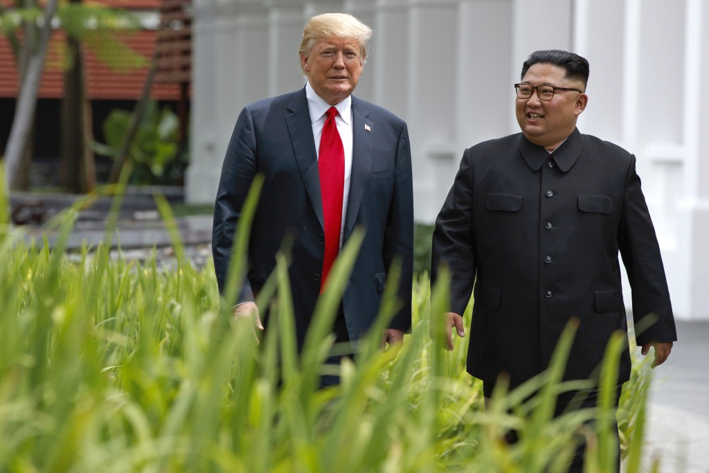 FILE - In this June 12, 2018 file photo, President Donald Trump walks with North Korean leader Kim Jong Un on Sentosa Island, in Singapore. South Kore...