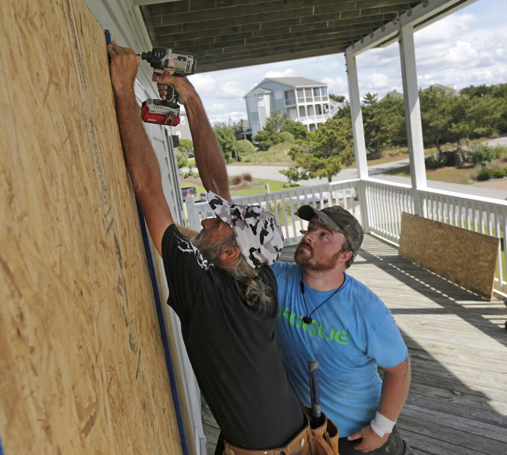 FILE - In this Wednesday, Sept. 12, 2018 file photo, Joe Gore, left, and Joshua Adcock prepare for Hurricane Florence as they board up windows on a ho
