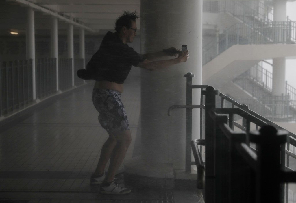 A man takes pictures against strong winds from Typhoon Mangkhut on the waterfront of Victoria Habour Hong Kong, Sunday, Sept. 16, 2018.  (AP Photo/Vin