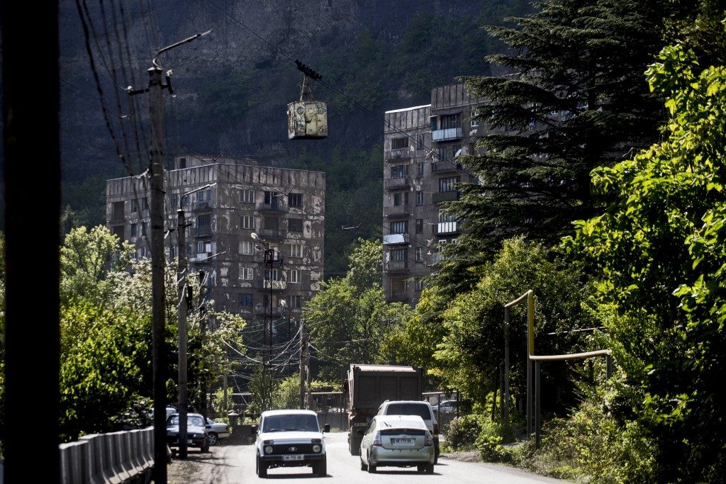 In this photo taken on Thursday, Aug. 30, 2018, a cable car moves between two buildings over a street in the Georgian city of Chiatura, about 200 kilo...