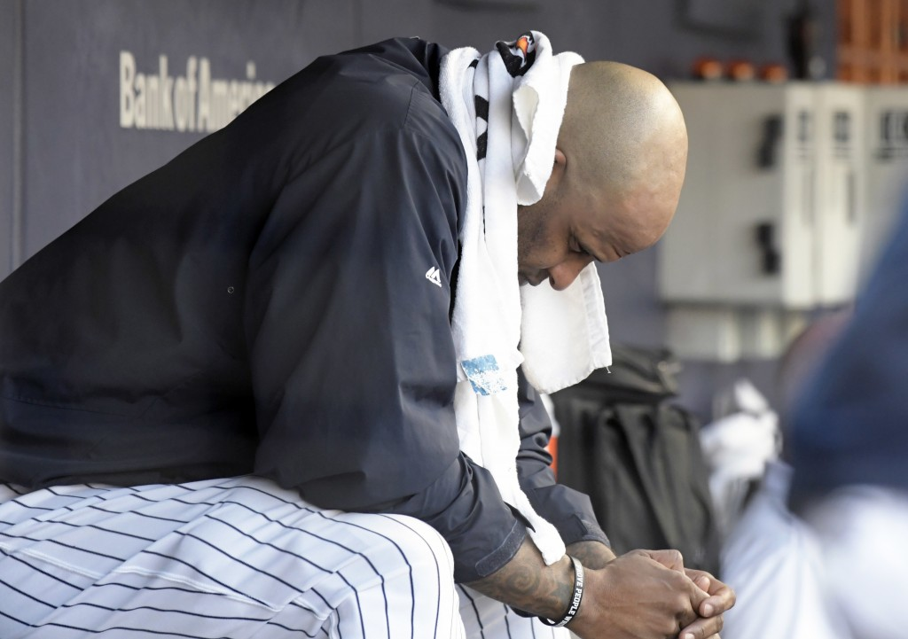 New York Yankees pitcher CC Sabathia sits on the bench after being taken out during the third inning of a baseball game against the Toronto Blue Jays