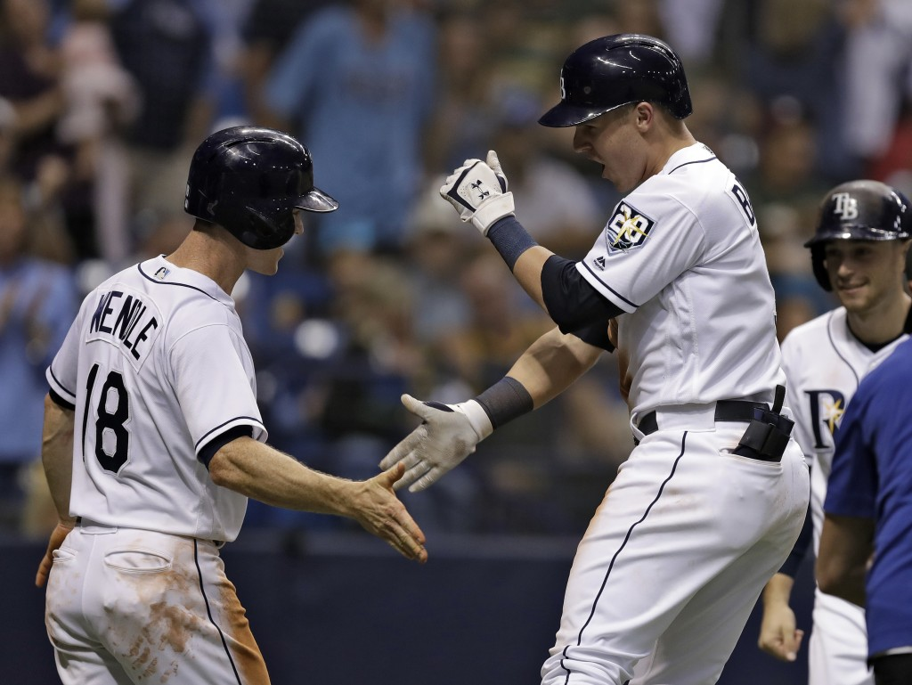 Tampa Bay Rays' Jake Bauers, center, celebrates with Joey Wendle, left, and Brandon Lowe, right, after Bauers hit a three-run home run off Oakland Ath