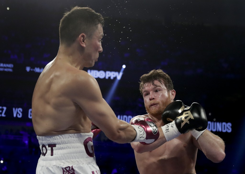 Gennady Golovkin, left, and Canelo Alvarez trade punches in the second round during a middleweight title boxing match, Saturday, Sept. 15, 2018, in La