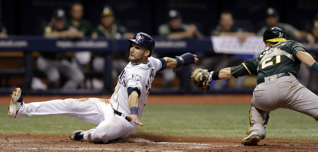 Tampa Bay Rays' Kevin Kiermaier, left, slides around a tag by Oakland Athletics catcher Jonathan Lucroy to score on a sacrifice fly by Jake Bauers dur