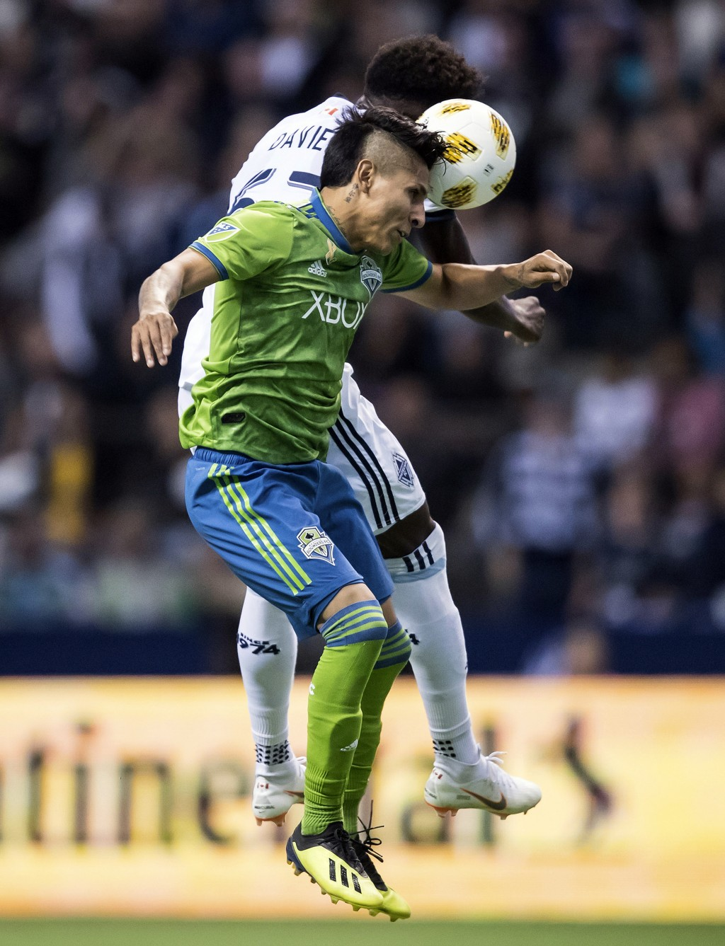 Seattle Sounders' Raul Ruidiaz, front, and Vancouver Whitecaps' Alphonso Davies vie for the ball during the first half of an MLS soccer match, Saturda
