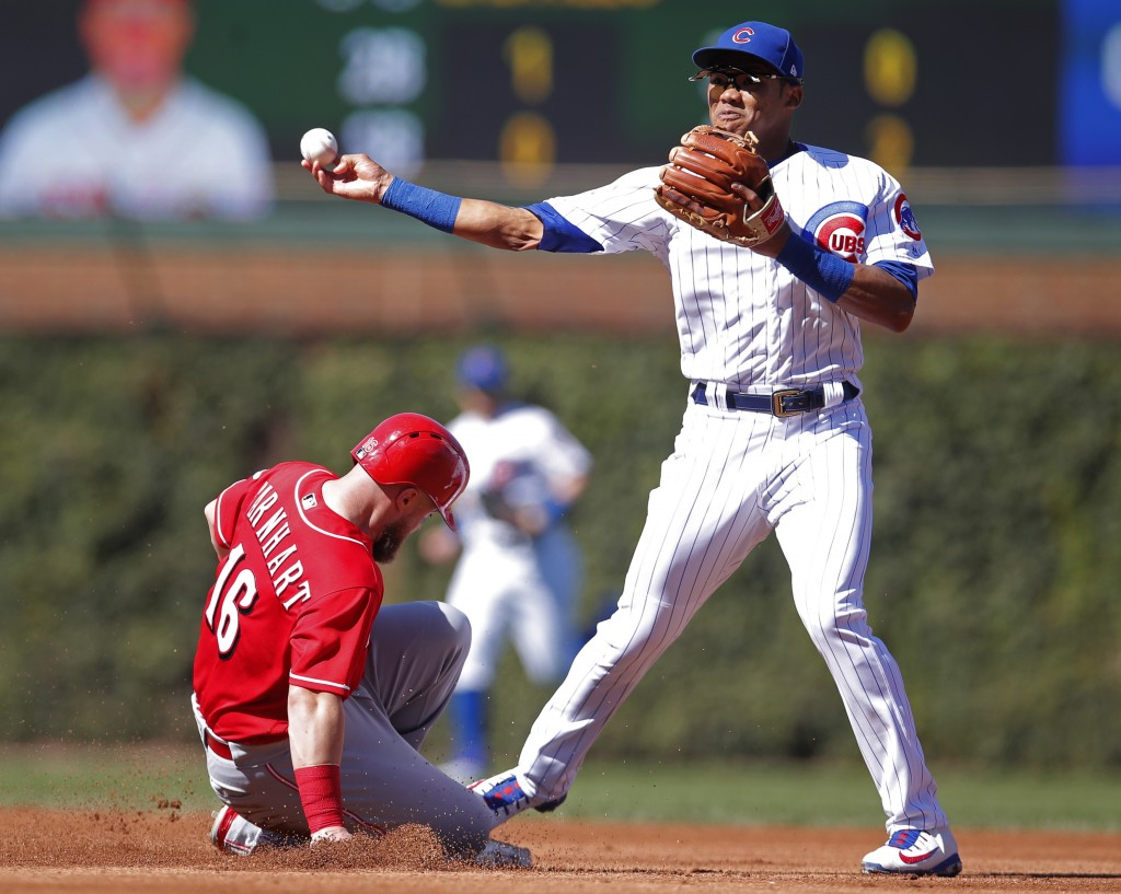 Cincinnati Reds' Tucker Barnhart, left, is out at second base as Chicago Cubs' Addison Russell makes the throw to first base during the fourth inning ...