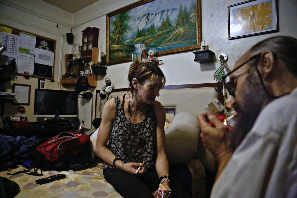 Jessie Kruger, left, a former heroin user who quit more than a year ago after a scary episode, prepare to have a cigarette sitting in her bedroom, Wed