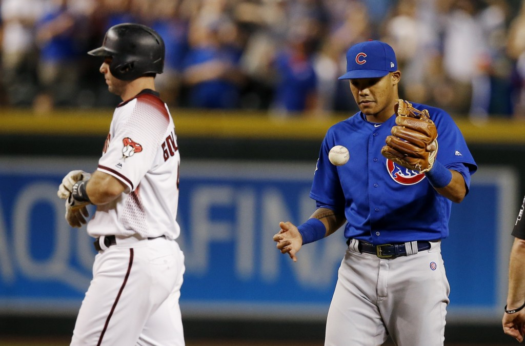 Chicago Cubs shortstop Addison Russell, right, flips the ball in the air after tagging out Arizona Diamondbacks' Paul Goldschmidt, left, trying to ste...