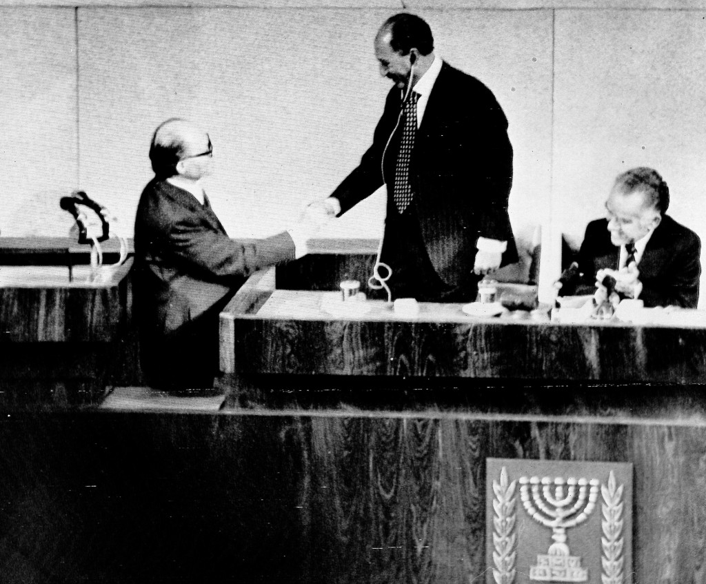 FILE - In this Nov. 20, 1977, file photo, Egyptian President Anwar Sadat, standing, shakes hands with Israel Prime Minister Menachem Begin in the Isra