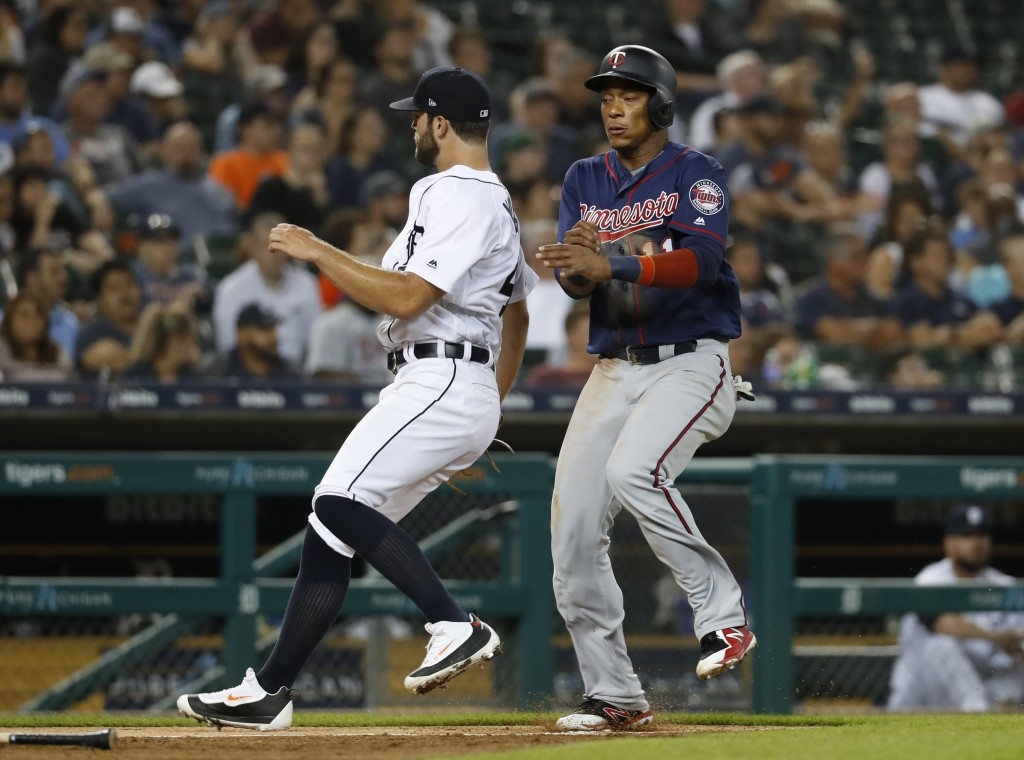 Minnesota Twins' Jorge Polanco, right, avoids Detroit Tigers pitcher Daniel Norris while scoring during the sixth inning of a baseball game in Detroit
