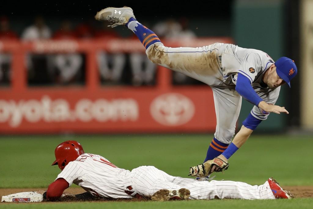 New York Mets second baseman Jeff McNeil, top, cannot reach Philadelphia Phillies' Cesar Hernandez as Hernandez steals second during the first inning ...