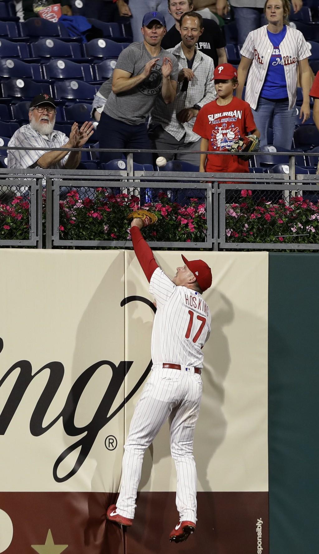 Philadelphia Phillies left fielder Rhys Hoskins cannot reach a home run by New York Mets' Steven Matz during the third inning of a baseball game Tuesd...