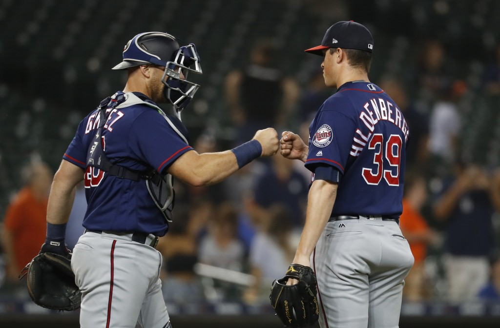Minnesota Twins catcher Chris Gimenez and relief pitcher Trevor Hildenberger (39) celebrate the final out of the team's baseball game against the Detr