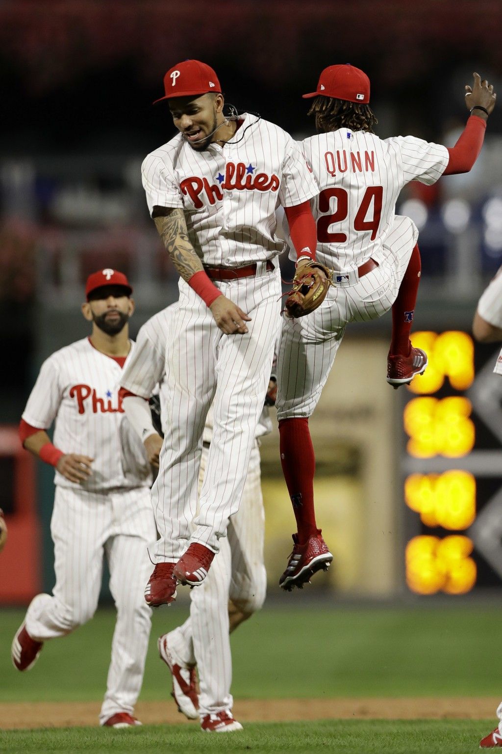 Philadelphia Phillies' J.P. Crawford, center, and Roman Quinn celebrate after a baseball game against the New York Mets, Wednesday, Sept. 19, 2018, in...