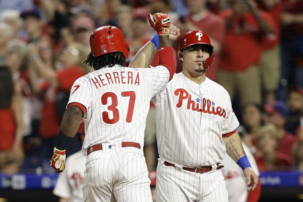 Philadelphia Phillies' Wilson Ramos, right, and Odubel Herrera celebrate after Herrera's two-run home run off New York Mets starting pitcher Noah Synd...