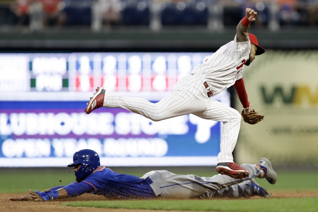 New York Mets' Amed Rosario, bottom, steals second base under the leaping tag from Philadelphia Phillies shortstop J.P. Crawford during the third inni...