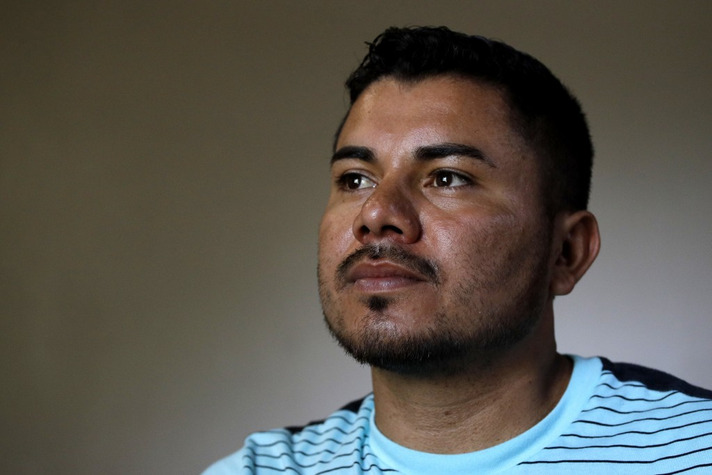 In this photo taken Tuesday, Aug. 28, 2018, Louis Alberto Enamorado Gomez stands in the living room of his home in Grandview, Mo. Living in the U.S. s...