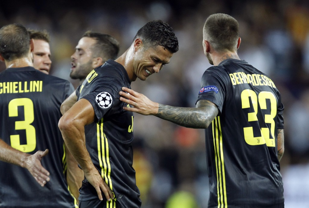 Juventus forward Cristiano Ronaldo is consoled by teammate Federico Bernardeschi, right, after receiving a red card during the Champions League, group