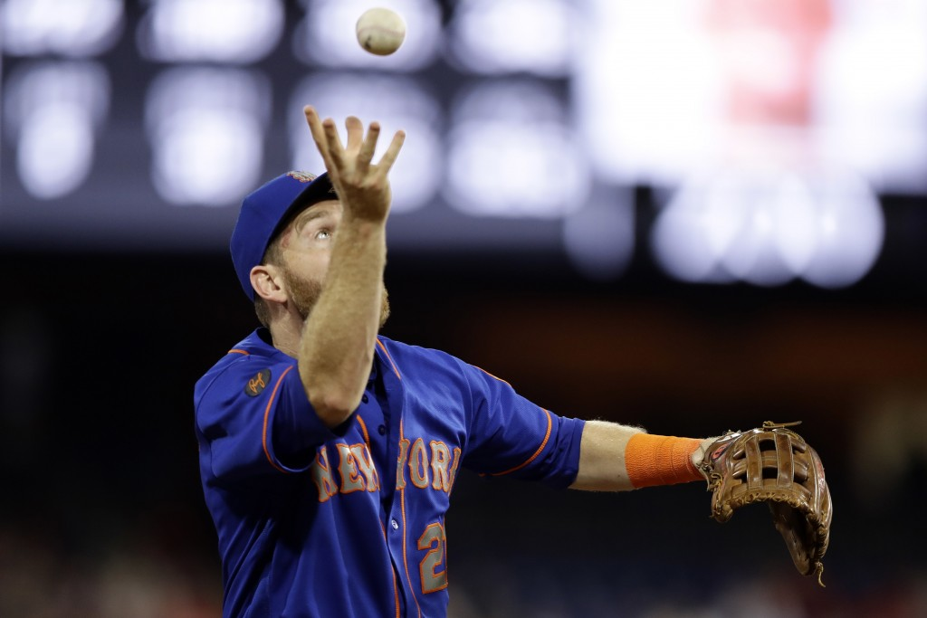 New York Mets third baseman Todd Frazier reaches for a loose ball after committing a fielding error on drive by Philadelphia Phillies' Aaron Altherr d...