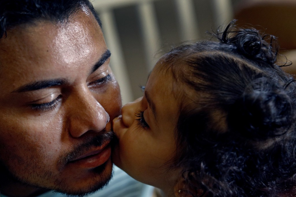 In this photo taken Tuesday, Aug. 28, 2018,  Louis Alberto Enamorado Gomez gets a kiss from his daughter, Jeydi, 1, at their home in Grandview, Mo. Li