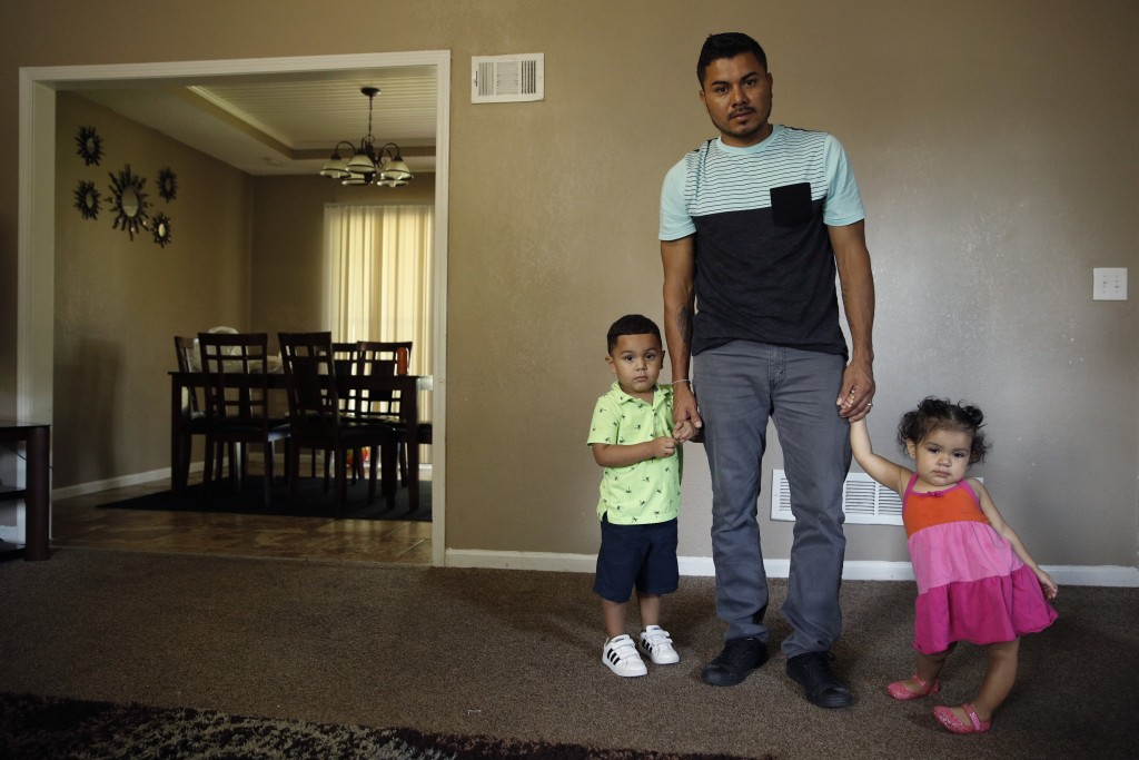 In this photo taken Tuesday, Aug. 28, 2018, Louis Alberto Enamorado Gomez stands with his daughter, Jeydi, 1, and son, Justin, 3, at their home in Gra...