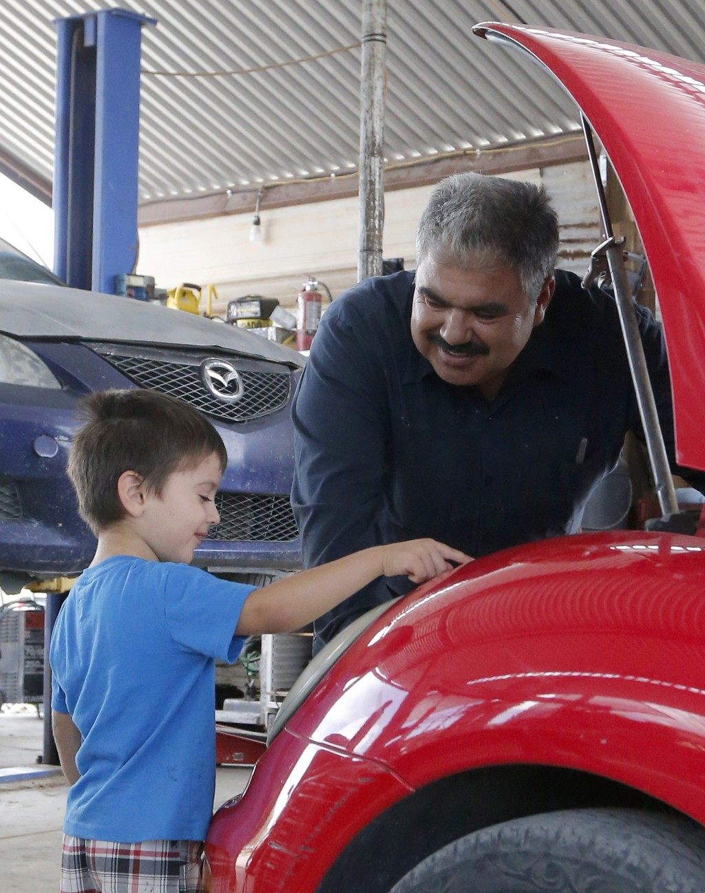 Ruben Moyoroqui, right, talks with his son, Rafael, in his auto repair shop in Tucson, Ariz., on Tuesday, Sept. 4, 2018. Moyoroqui, who came to the U.