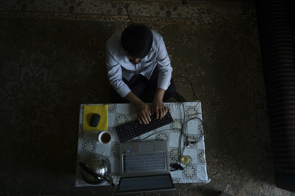 In this Aug. 24, 2018, photo, Abdurehim Imin, 42, father to 5 children and a poet and writer from Kashgar, China, works on an autobiography at his hom...