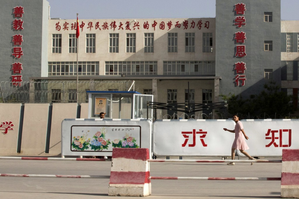 In this Aug. 31, 2018, photo, a woman walks past the Kashgar Dongcheng No. 4 Junior Middle School, which is part of a cluster of schools with slogans ...