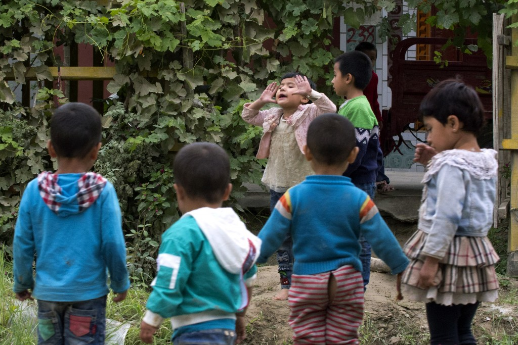 In this Aug. 30, 2018, photo, Uighur children play outdoors in Hotan, in western China's Xinjiang region. Uighurs fear the Chinese government's expans...