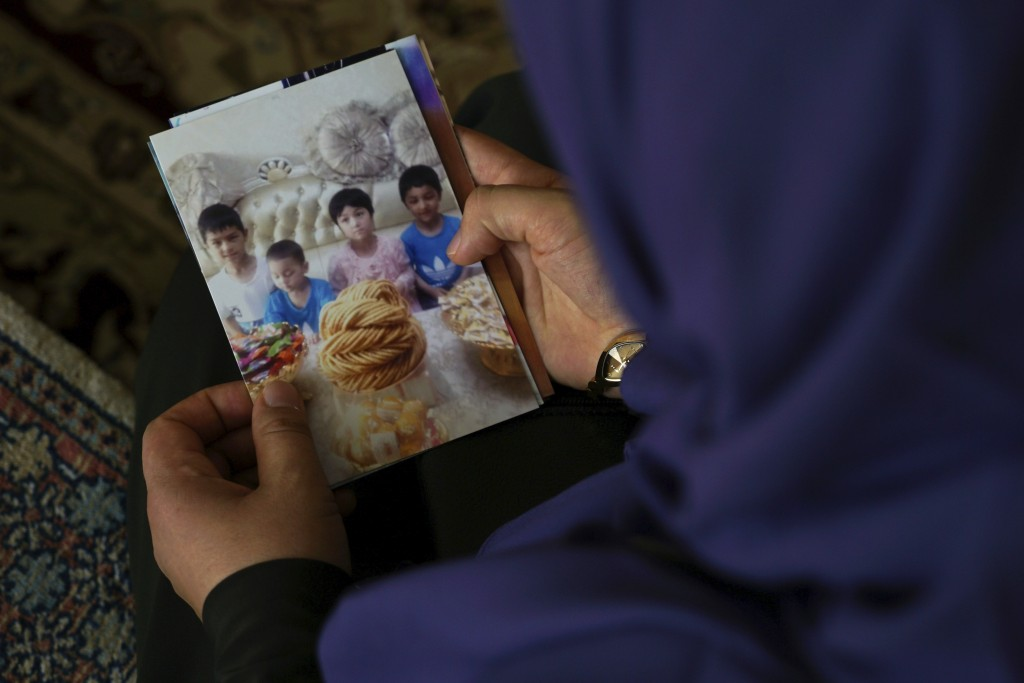 In this Aug. 20, 2018, photo, Meripet, 29, holds on to a photograph of her children in Istanbul, Turkey. Meripet came to Turkey in February 2017 to vi...
