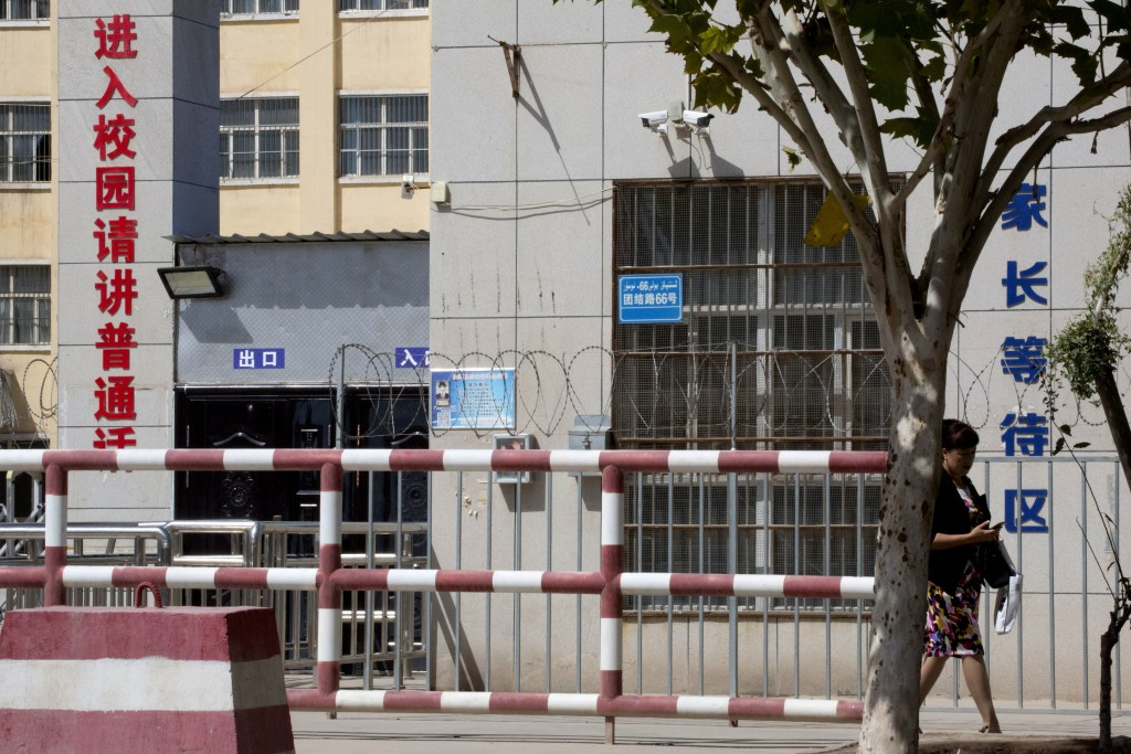 In this Aug. 31, 2018, photo, a woman walks past the entrance to the No. 4 High School also known as the Peyzawat Bilingual High School with signs whi...