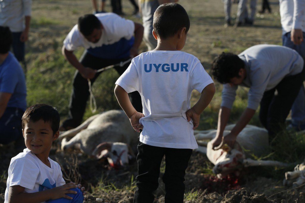 """In this Aug. 21, 2018, photo, members of the Uighur community watch as others slaughter sheep following prayers at the start of the Eid al-Adha, or """"F..."""