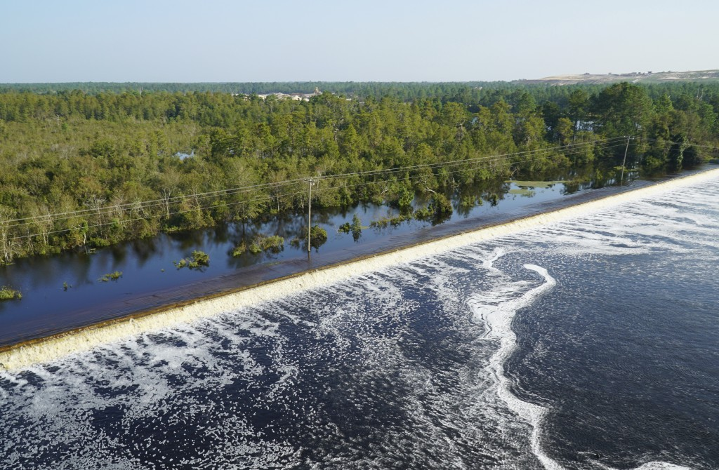 In this drone photo released by Duke Energy, flooding from the swollen Cape Fear River overtops an earthen dike at Sutton Lake, a 1,100-acre (445-hect