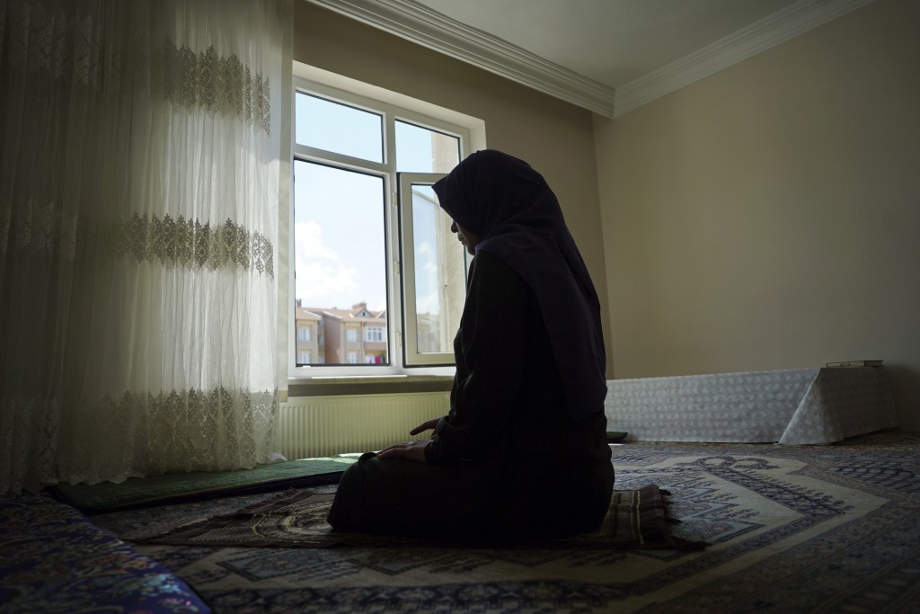 In this Aug. 20, 2018, photo, Meripet, 29, prays at her home in Istanbul, Turkey. Meripet came to Turkey in February 2017 to visit her sick father, le...