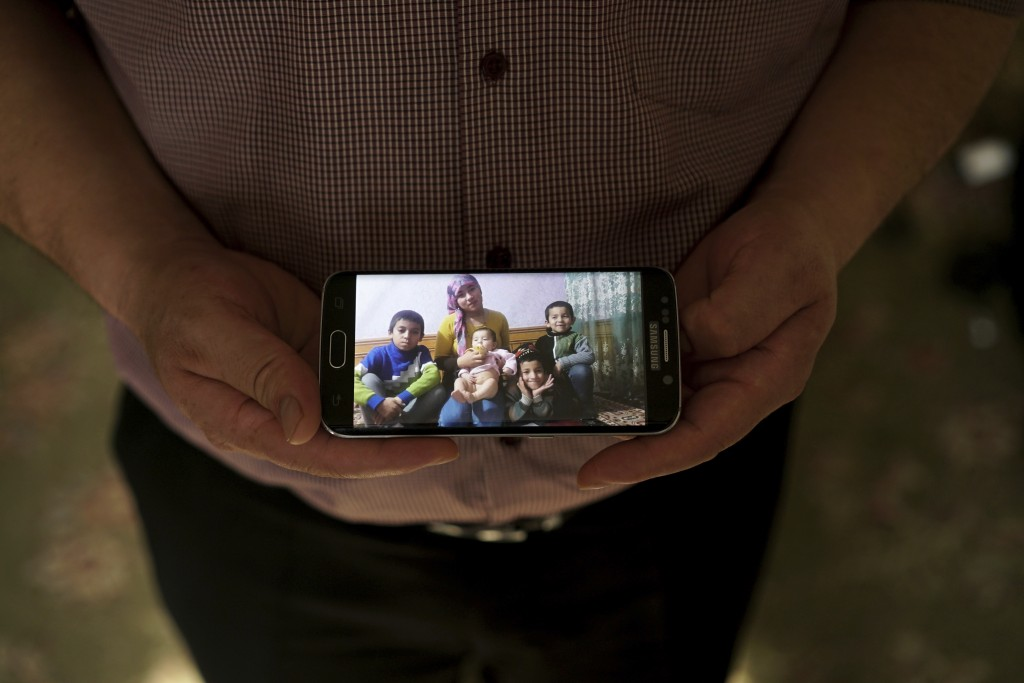 In this Aug. 23, 2018, photo, Adil, 42, father to five children and a businessman from Kashgar, China, holds a phone showing an image of his family le...