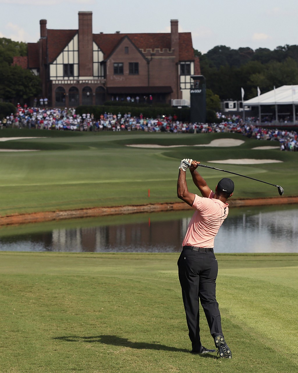 Tiger Woods hits his fairway shot to the 18th green during the first round of the Tour Championship golf tournament Thursday Sept. 20 2018 in Atlan