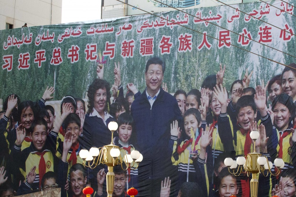 """In this Aug. 31, 2018, photo, a propaganda poster showing Chinese President Xi Jinping with ethnic minority children and the slogan which reads """"Party..."""