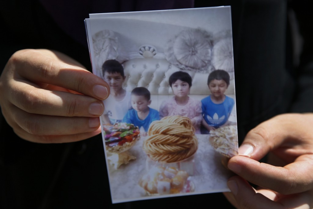 In this Aug. 21, 2018, photo, Meripet, 29, holds on to a photograph of her children in Istanbul, Turkey. Meripet came to Turkey in February 2017 to vi...
